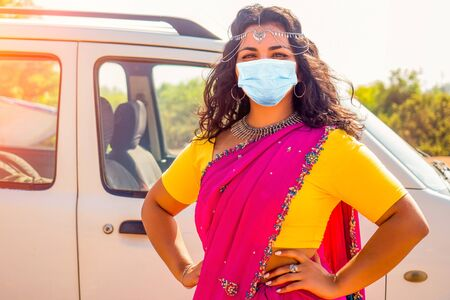 Portrait of young Indian woman in a traditional pink sari and costume jewelry on summer vacation day in new car
