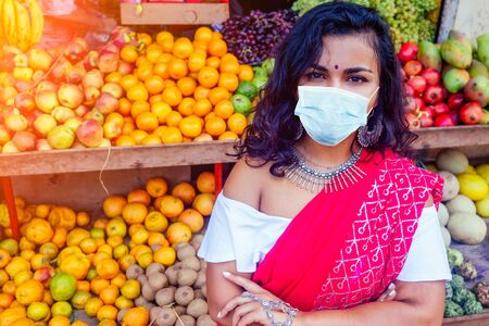 Portrait of beautiful traditional Indian seller business woman in red sari dress with customer in street Delhi market india mumbai.Happy girl shopper in a supermarket fruits vegetable shop Kerala Goa.