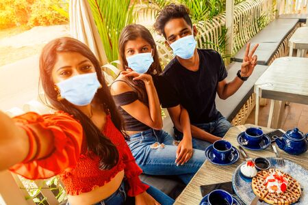 fashionable indian friends couple of two woman and man making selfie mobile phone.friends long-awaited meeting students eating pancake drinking masala tea after shopping.summer instahram lifestyle