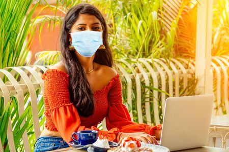 modern india woman working on laptop in coffee shop eating pancakes.online purchase black friday sale in summer outdoors park freelance freelancing surfing