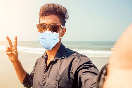 young hindu stylish man taking a picture self portrait on the smartphone front camera with sunglasses active beach vacation on semmertime happy Goa India beach. sunscreen spf protection concept.