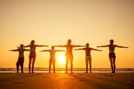 six health people in stand hatha position with hand up raced and breath full chest in Goa India beach at sunset .