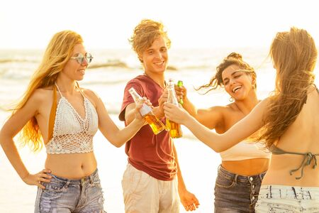 happy international friends drinking smoothie juice from glass bottle on the beach Stockfoto