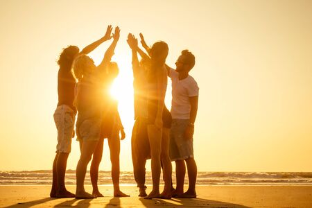 group of friends enjoying sunset in Goa India high five .