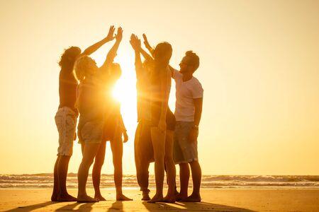 Gruppe von Freunden genießen den Sonnenuntergang in Goa Indien High Five.
