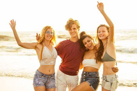 Un groupe d'amis multiethnique danse à la plage