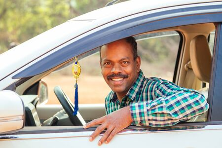 indian man sitting behind the wheel looking at camera and smile