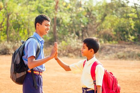 two indian brothers meeting at school and giving high five in Goa outdoors