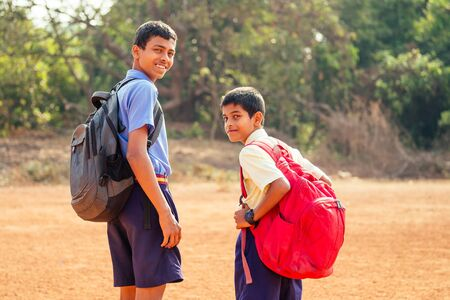 two indian brothers going to school in Goa outdoors