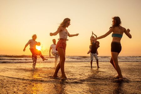 multicultural multinational happy people running into the sun carefree and happiness, vacation on sea. Archivio Fotografico