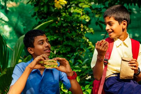 indian school boy eating sandwich and his friend with backpack sits on table and eating an apple in park