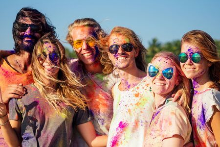 mixed race friends having fun with colors on seaside outdoors in Goa India Imagens