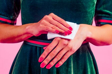girl using wet wipes the sweat hand applying hand sanitizer on a pink background in the studio