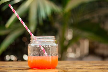 coctail jar with straw eco paper in tropical park.