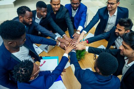 top view of team work high five a group of successful afro americans, europeans ,arabic and korean businessman and businesswoman working Standard-Bild