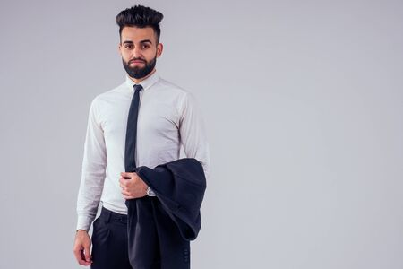 young turkish handsome black hair man in stylish business suit knotting the tie in studio isolate white background