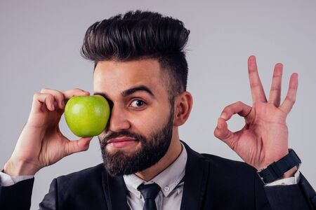young handsome black hair man in stylish business suit eating green apple in studio isolate white background