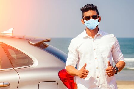 Indian businessman in car outdoors on sea beach summer good day.a man in a white shirt and mask rejoicing buying a new car enjoying a vacation by the ocean