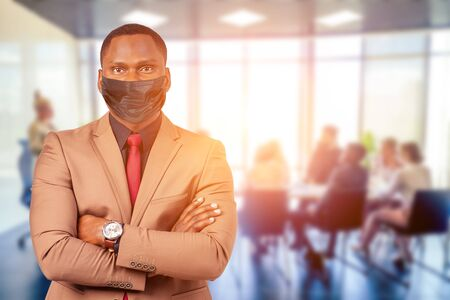 focus on man in medical mask , a group of successful afro americans, europeans ,arabic and korean businessman and businesswoman working in the office with large glass windows background