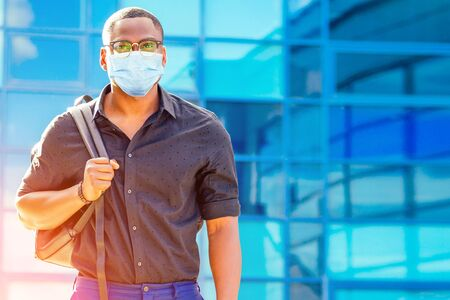 handsome trendy African American university lecturer male with glasses in stylish clothes black shirt with a backpack on the shoulders stand background of the blue windows