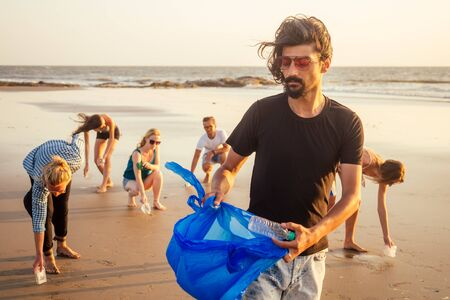 handsome indian man in the foreground collecting plastic from sand into the bag , his mixed race friends picking waste on background in Goa India beach.
