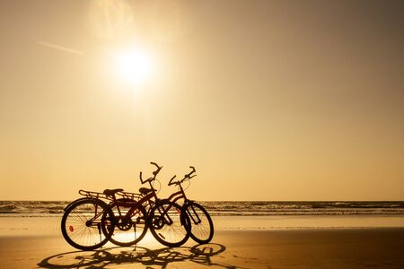 two bicycles and empty beach without people.no body at sunset