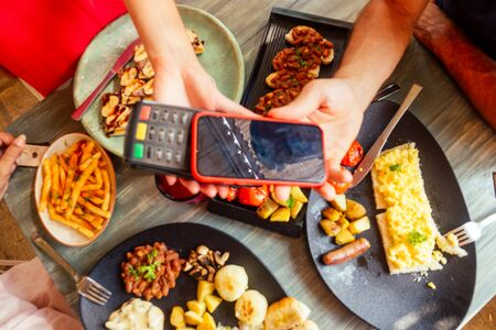 indian man paying in restaurant by credit card app on smartphone reader