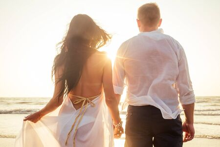 Vacation couple walking on beach together in love at sunset goa