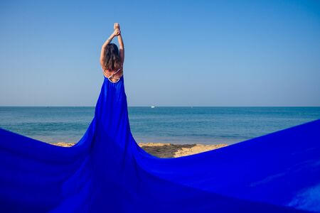 woman in amazing blue dress feeling free and happy yo be at ocean