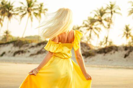 woman in amazing yellow dress feeling free and happy yo be at ocean Reklamní fotografie
