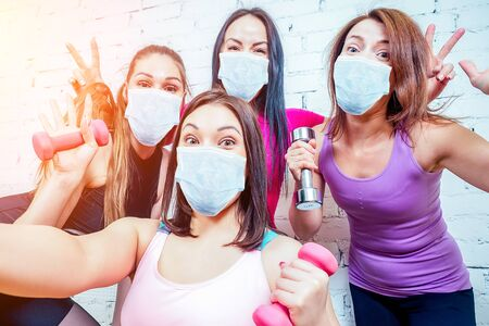 four beautiful and young women girlfriends in medical mask are photographed selfie on the phone in sportswear in the gym. group portrait of a woman self having fun with dumbbells