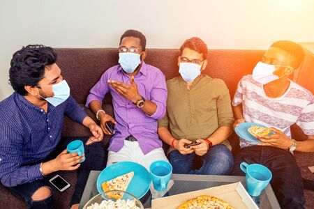 four african american males in medical mask eating pizza at home party,throwing popcorn into each other