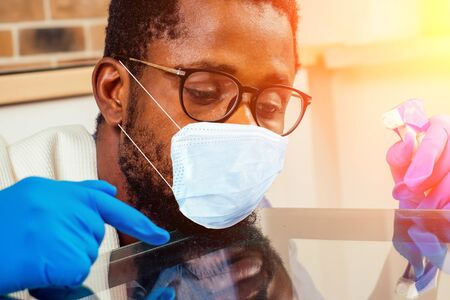 african man in medical mask cleaning cooktop cooker hood at home ,Brick wall background