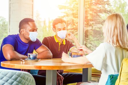 multinational group of happy friends in medical mask enjoy and drinking tea cafe