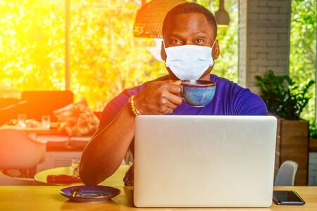 Portrait of a smiling businessman with laptop at cafe drinking tea alone in medical mask Zdjęcie Seryjne