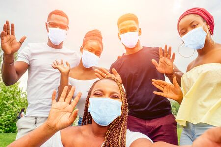 group of five friends female and male in medical mask taking selfie on camera smartphone and having fun outdoors lifestyle near lake
