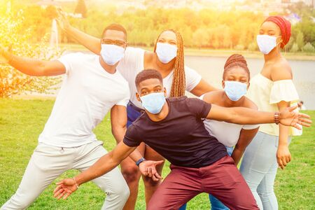 group of five smiling african-american men and women in medical mask walking outside cloudy weather near the lake,exchange students in Russia