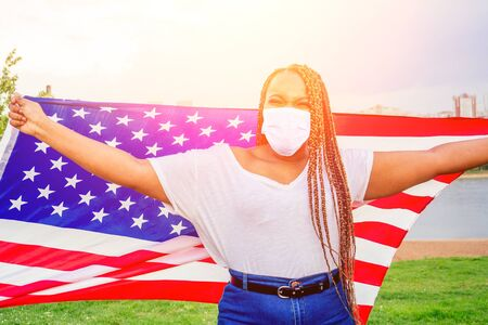 Smiling afro american woman holding USA flag and looking at camera in medical mask autumn evening spring in the park by the lake Reklamní fotografie