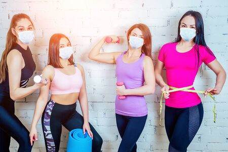 a group of four beautiful and sportive women in medical mask warming up and posing against a white brick wall in the gym. the concept of teamwork and fitness