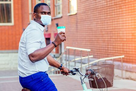 stylish and young African American man in medical mask holding a glass with coffee sitting on a bike in the summer park