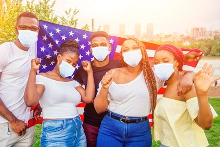 Group of girls and boys in medical mask smiling with American flag in spring park autumn evening learning English language exchange students Reklamní fotografie