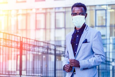 handsome and stylish afro american businessman in a fashionable jacket and a white shirt with a collar background of Manhattan glass offices cityscape