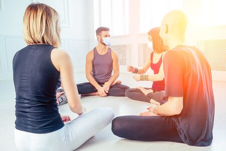 a happy group of men and women practicing yoga in the studio in medical mask. the concept of new lifestyle pandemic. coach and students in a circle Reklamní fotografie