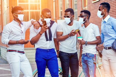 fashionable friends at a meeting. a group of five handsome African American men well-dressed in medical mask businessmen having fun and communicating in the summer in the park Reklamní fotografie