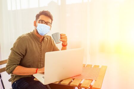 Asian businessman freelancer in medical mask working with a laptop and drinking coffee from blue cup at veranda balcony.freelance and remote work Reklamní fotografie