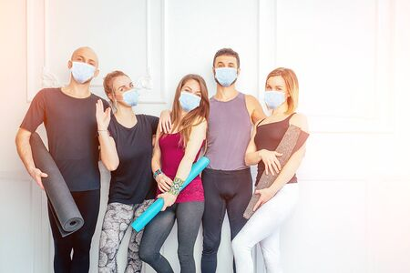 a happy group of men and women practicing yoga in the studio in medical mask. the concept of new lifestyle pandemic. coach and students after traning