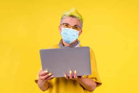 mature old woman with colored stylish yellow dyed hair in warm dress and medical mask holding modern laptop background studio