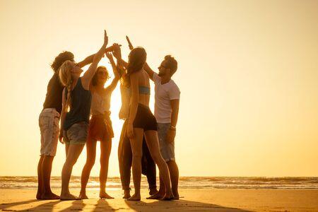 A group of friends enjoying sunset in Goa India high five Reklamní fotografie