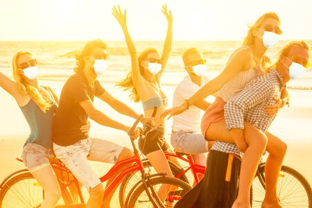 happy friends contest on cycle and sporty man giving their girlfriend piggyback rides summer freedom holiday on sea