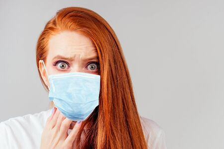 redhair ginger woman feeling unhappy and wearing medical mask Reklamní fotografie